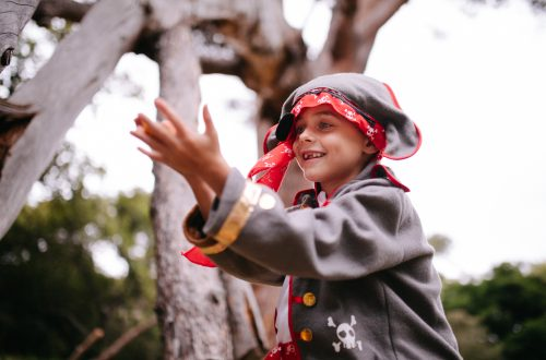 Child dressed up as pirate smiling excited. His toothy smile is missing some teeth
