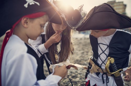 Three little pirates, a girl aged 11 and two boys aged 7 are playing pirates on the beach. They are trying to read ancient treasure map that leads to ... a treasure. Sunny summer day. Nikon D800